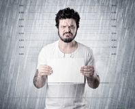 Caught gangster in jail. Gangster with rainy, lowering background and table on his hand Royalty Free Stock Image