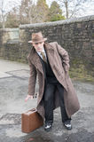 Gangster with a suitcase, posing outdoors. royalty free stock image