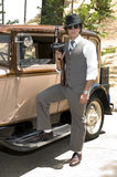 Gangster with Tommy gun. Young man dressed as a gangster, holding a Tommy gun in his right hand, standing next to a 1930 Model A vintage car with his foot on the stock image