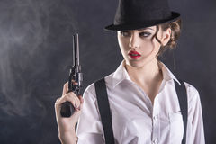 Gangster Woman. Beautiful and dangerous. Young female gangster holding the gun. isolated on dark background royalty free stock photo