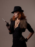 Gangster woman in fedora hat. And evening dress holding mouthpiece royalty free stock photo