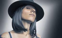 Gangster woman with hat and black hair. On blurry background stock images