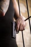 Gangstermann, der Gewehr steht und hält Stockfotos