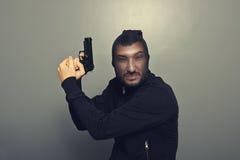 Gangstermann mit Gewehr über Grau Lizenzfreie Stockfotografie