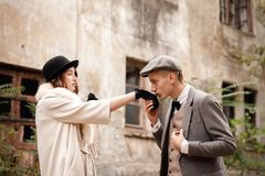 Gangsters. Against the background of an abandoned building in the forest, a man kisses a woman`s hand. royalty free stock photography