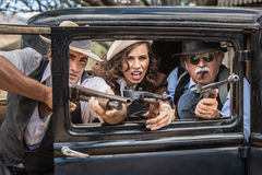 Gangsters Shooting From Car. Vintage gangsters shooting machine guns from car door Royalty Free Stock Photography