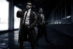 Gangsters. Two dangerous man wearing leather coats,black sunglasses, classic white shirts with black tie-necks, are full-length standing in dark place ready for Royalty Free Stock Image