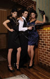 Gangsters who share the money,. A guy and two beautiful young women in the image of gangsters with guns Stock Photography