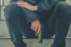 Gangsterscy mężczyźni trzyma armatniego obsiadanie na schodkach Młodego człowieka pokojowy obsiadanie z pistoletem na on ręka sam zdjęcie stock