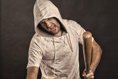 Gangsterski krzyk z nietoperz bronią Brodaty m??czyzna chwyta kij bejsbolowy Gniewny chuligański odzież kapiszon w hoodie tshirt  fotografia royalty free