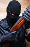 Gangsterterrorist-Mafiaverbrecher mit einem Gewehr Stockfoto