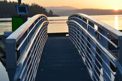 Gangway to marina at sunset. Aluminum gangway leading to marina with waterway landscape at sunset Royalty Free Stock Photo