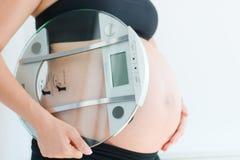 Ganho de peso durante a gravidez com a escala da terra arrendada da mulher gravida Foto de Stock