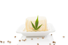 Ganja butter with leaf. On white saucer on white background. Hemp butter. Alternative remedy royalty free stock photo