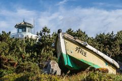 Ganjeolgot Lighthouse with broken boat in front inside nature near coastline. Easternmost Point of Peninsula in Ulsan, South Korea royalty free stock photos