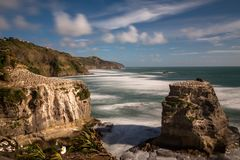 Gannett colony on the rocks above Muriwai Beach on the West coast of New Zealand, long exposure to smooth out the water and give stock photos