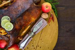 Gans gebacken im Ofen mit Äpfeln Weihnachtsgans auf einem hölzernen Behälter Lizenzfreies Stockfoto
