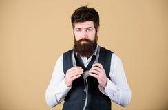 Ganska formellt trendig man Skäggig man som binder en slips Brutal caucasian man som justerar modetillbeh?ren 308 m?ssingskassett royaltyfri bild
