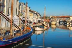 Ganska kiosk för jul på invallningen av portkanalen med de typiska fiskebåtarna av Adriatiskt havet Arkivfoto