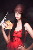 Ganster And Her Gun. Sexy but sinister female gangster wearing a hat and red dress displaying her gun and ill gotten loot Royalty Free Stock Photo