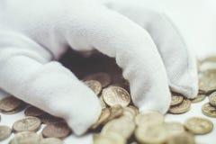 Gant blanc avec des pièces de monnaie image stock