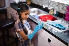 Gant de port de fille mignonne tout en se tenant dans la cuisine photographie stock libre de droits