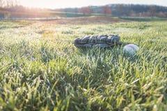 Gant et boule de base-ball sur le champ d'herbe avec l'augmentation du soleil Photo libre de droits