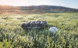Gant et boule de base-ball sur le champ dans le matin Images stock