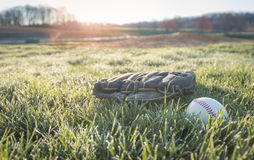 Gant et boule de base-ball sur le champ dans le matin Photographie stock libre de droits