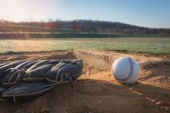 Gant et boule de base-ball sur le monticule du ` s de broc Image libre de droits