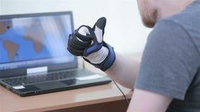 Gant robotique électronique de cyber L'homme joue le jeu de VR opérant avec le gant bionique du simulateur 3D banque de vidéos