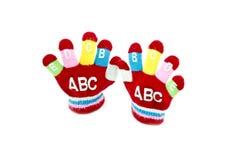 Gant rouge d'enfants avec le mot ABCDEFGIJ Photographie stock libre de droits