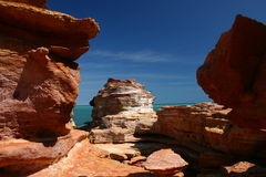 Gantheum Point Rocks - Broome. Landscape view of scultured red rocks framing a glimpse of a turquoise sea with a highly contrasting brilliant blue sky with a stock photography