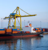 Gantry crane lifts containers onto cargo ship. Cargo ship in port with lots of activity as cranes life containers onto vessel Royalty Free Stock Images