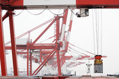 Gantry Crane Loads Container Ship. View from the deck of a cargo freighter as a gantry crane loads or unloads a shipping container Royalty Free Stock Image
