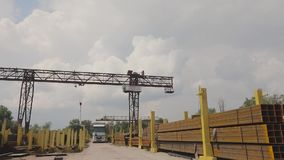 A gantry crane loads metal into a truck, loads metal in a warehouse, a large gantry crane, people work in a metal. Warehouse, panorama, workers stock video footage