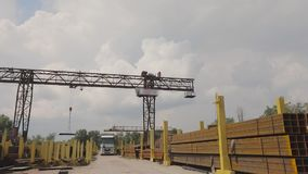 A gantry crane loads metal into a truck, loads metal in a warehouse, a large gantry crane, people work in a metal. Warehouse, panorama, workers stock footage