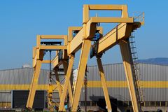Gantry cranes in front of a gray and yellow building of a manufacturing factory Stock Photo