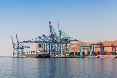 Gantry cranes unload container ship. Aqaba, Jordan - May 18, 2018: Gantry cranes unload container ship Northern Dependant. Aqaba container terminal at sunny royalty free stock photo