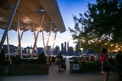 Gantry Plaza State Park on a summer evening. LONG ISLAND CITY, NEW YORK - JULY 13, 2019:  View at Gantry Plaza State Park on a summer evening with people visible stock photography