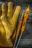 Gants électriques de sécurité de cuir d'appareil de contrôle sur le conseil en bois image stock