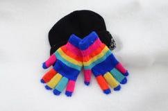 Gants colorés de Knit d'hiver sur la neige Photos libres de droits