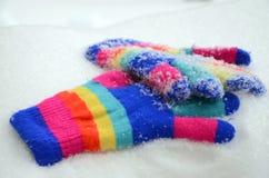 Gants colorés de Knit d'hiver sur une neige Photo stock
