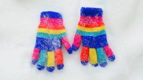 Gants colorés de Knit d'hiver sur une neige Image stock