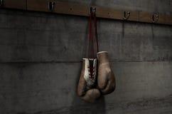 Gants de boxe accrochant dans la chambre de changement Photo stock