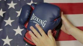 Gants de boxe d'enfants et un drapeau américain banque de vidéos
