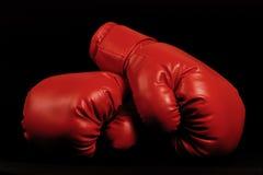 Gants de boxe de cru apparaissant du fond noir Images libres de droits