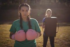Gants de boxe de port de femme déterminée pendant le parcours du combattant Photographie stock libre de droits