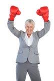 Gants de boxe de port de femme d'affaires et relèvement de ses bras images libres de droits