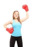 Gants de boxe de port heureux d'athlète féminin et triomphe de faire des gestes Photographie stock